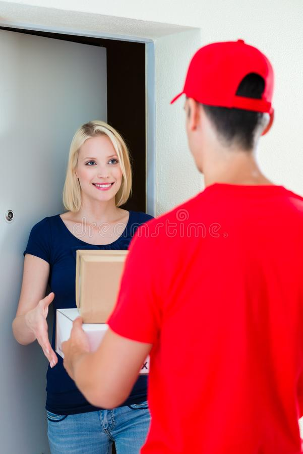 Young woman receiving package from delivery man. Smiling beautiful young women receiving the courier from delivery men at door royalty free stock photos