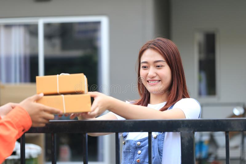 Young woman receiving parcel from delivery man bringing some pac. Kage at the home, shipping and postal service concept royalty free stock photo