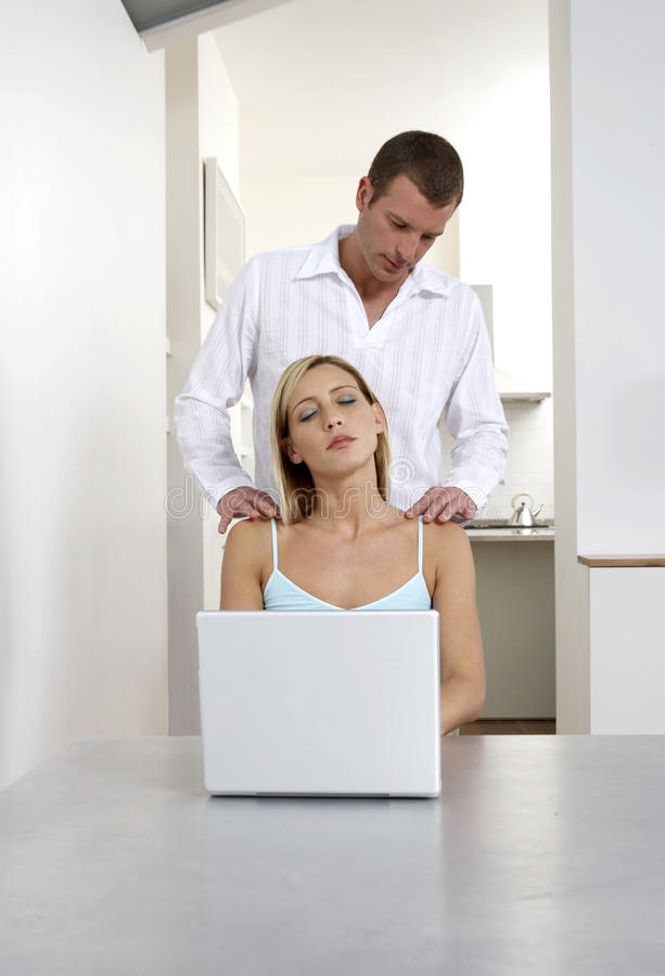 Young woman receiving a shoulder massage whilst working from home stock images