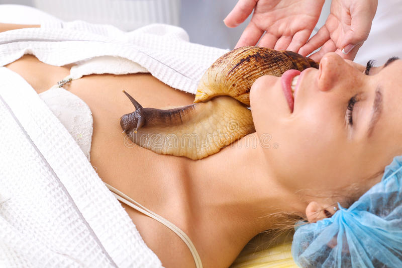 Young woman receiving snail neck massage. Snail on neck. Cleaning procedure in spa salon royalty free stock images