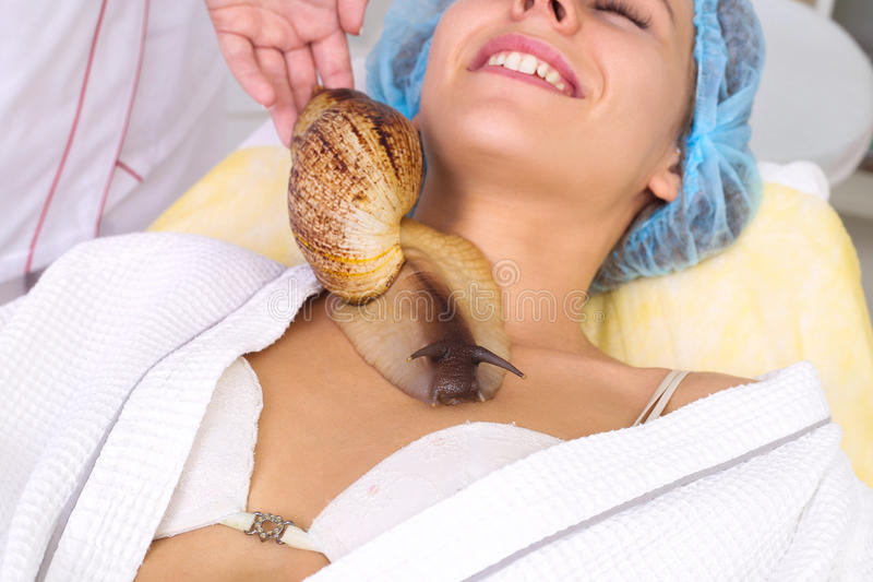 Young woman receiving snail neck massage. Snail on neck. Cleaning procedure in spa salon royalty free stock image