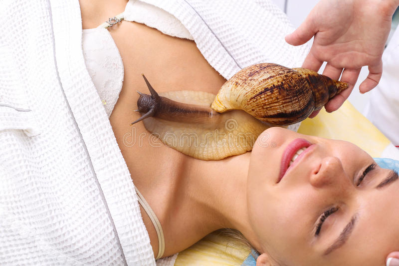 Young woman receiving snail neck massage. Snail on neck. Cleaning procedure in spa salon stock photography
