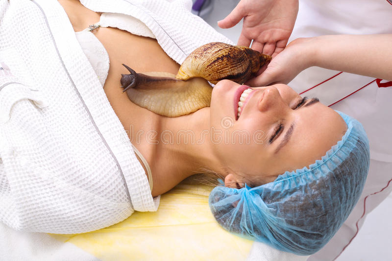 Young woman receiving snail neck massage. Snail on neck. Cleaning procedure in spa salon stock images