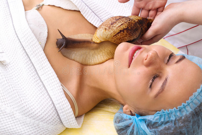 Young woman receiving snail neck massage. Snail on neck. Cleaning procedure in spa salon royalty free stock photos