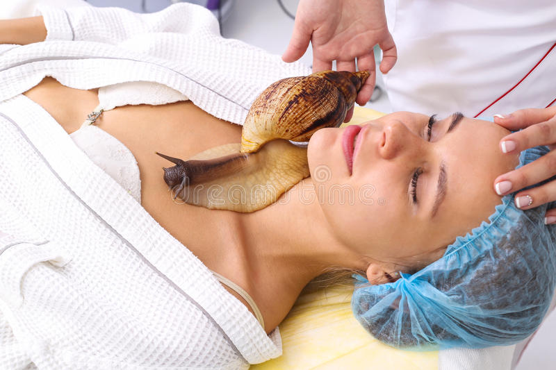 Young woman receiving snail neck massage. Snail on neck. Cleaning procedure in spa salon royalty free stock photography