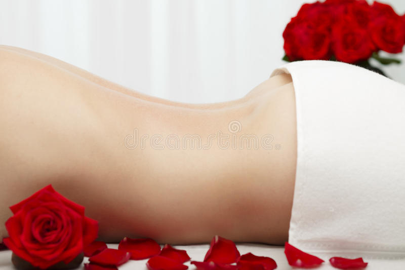 Young Woman Receiving Swedish Deep Tissue Massage Red Roses. Young woman is about to receive Swedish deep tissue, light, medium pressure massage. Indoors, with stock photography