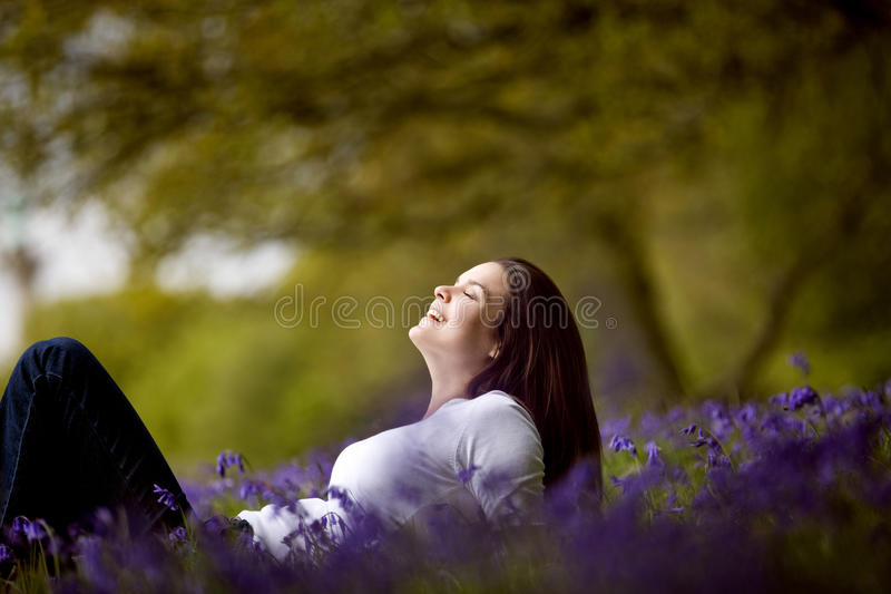 A young woman reclining with eyes closed in a field of bluebells stock photography