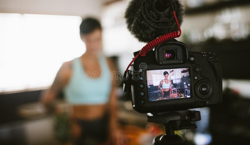 Woman recording content for her vlog in kitchen royalty free stock photo