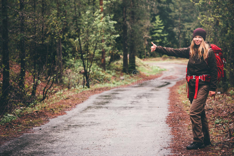 Young Woman with red backpack hitchhiking. Alone on the road Travel Lifestyle concept royalty free stock image