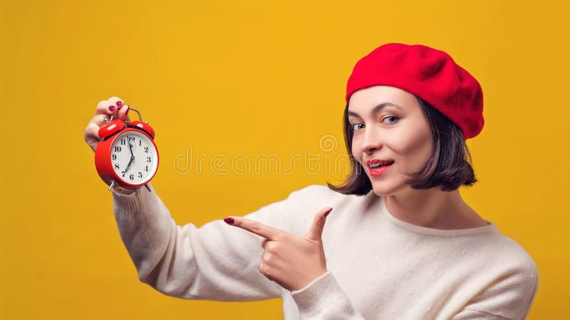 Young woman in red beret with alarm clock. Woman pointing on clock over yellow background. Girl shows the time on the clock. stock photo