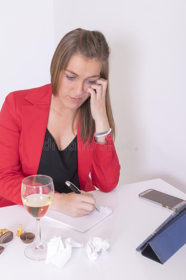 Young woman in red and black dress writing. Eating a chocolate praline and drinking white wine stock photo
