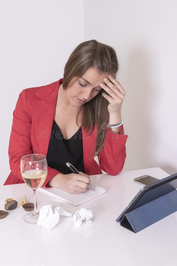 Young woman in red and black dress writing. Eating a chocolate praline and drinking white wine stock photography