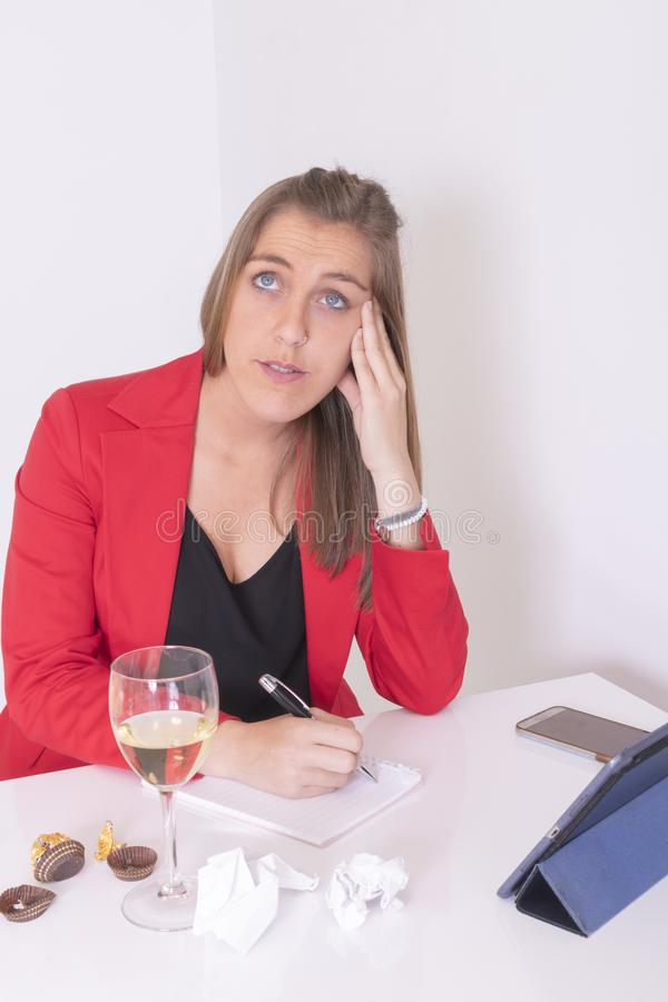 Young woman in red and black dress writing. Eating a chocolate praline and drinking white wine stock images