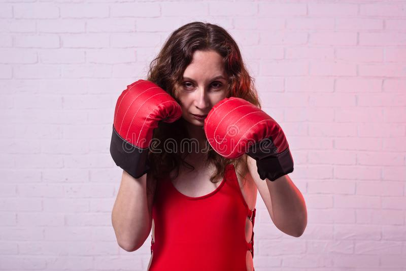Young woman in red boxing gloves on a pink background royalty free stock image
