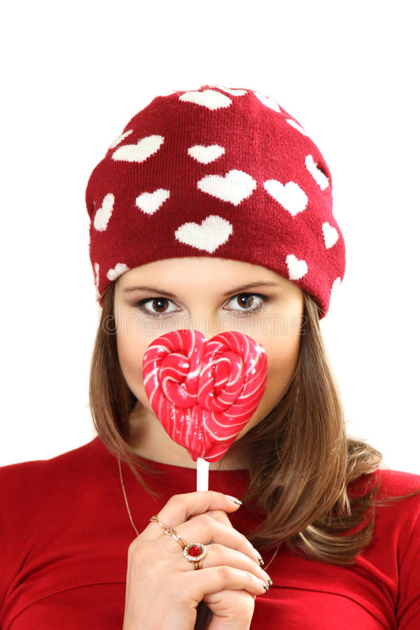 The young woman in a red cap with hearts and with sugar candy he. Art on a stick. white background royalty free stock photos