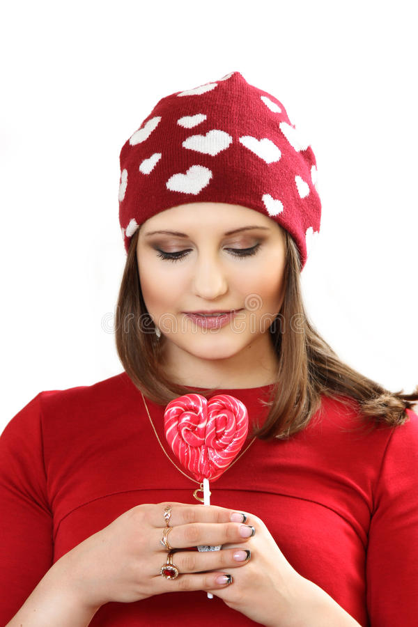 The young woman in a red cap with hearts and with sugar candy he. Art on a stick. white background royalty free stock photo