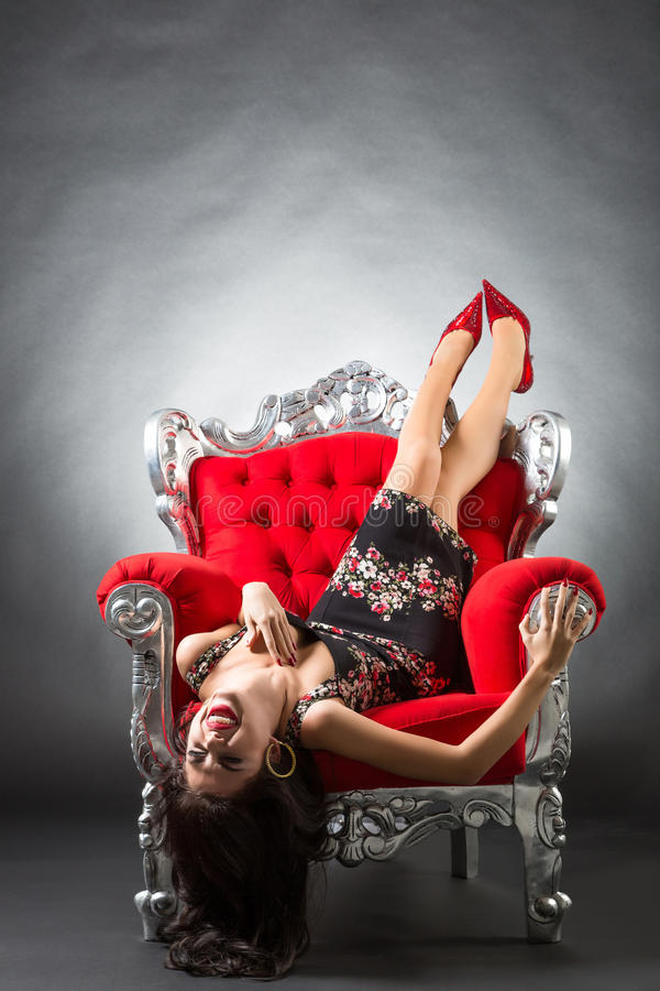 Young woman in a red chair. Retro style royalty free stock photo