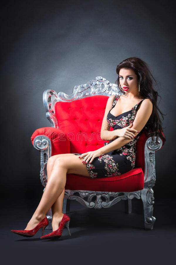 Young woman in a red chair. Retro style stock photos