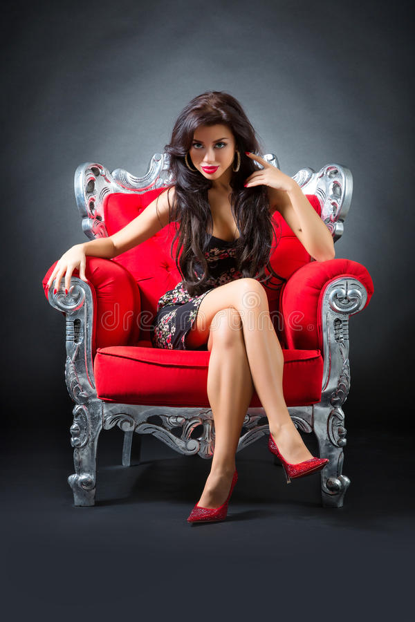 Young woman in a red chair. Retro style royalty free stock photos