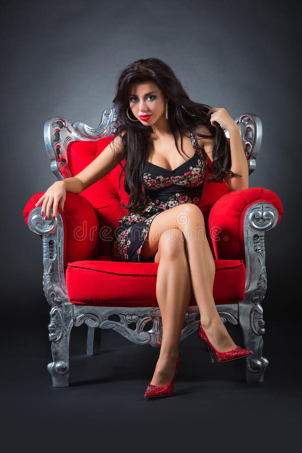 Young woman in a red chair. Retro style royalty free stock photography