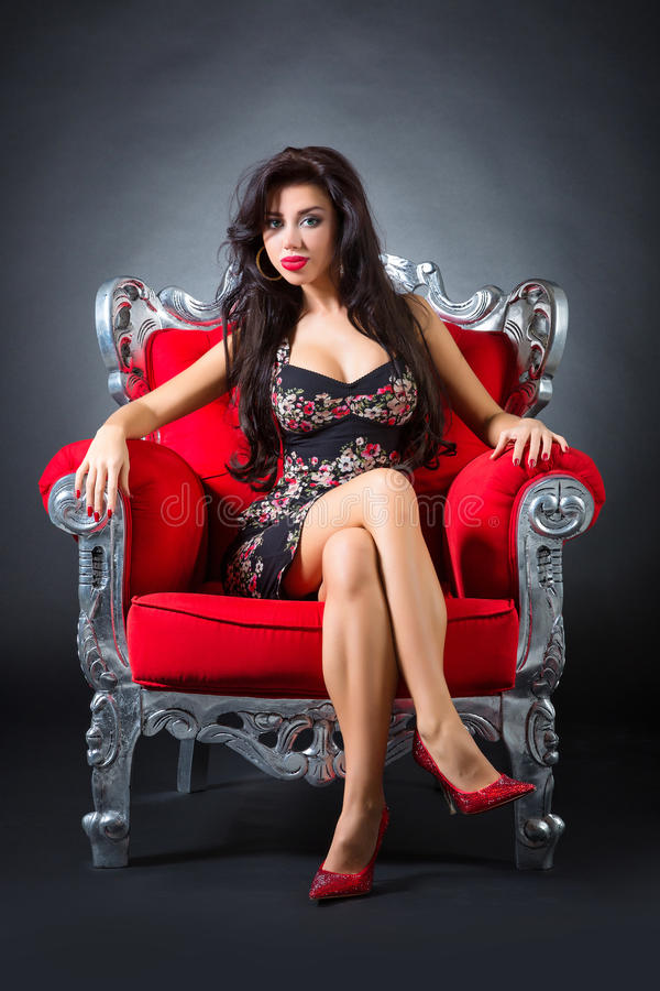Young woman in a red chair. Retro style royalty free stock images