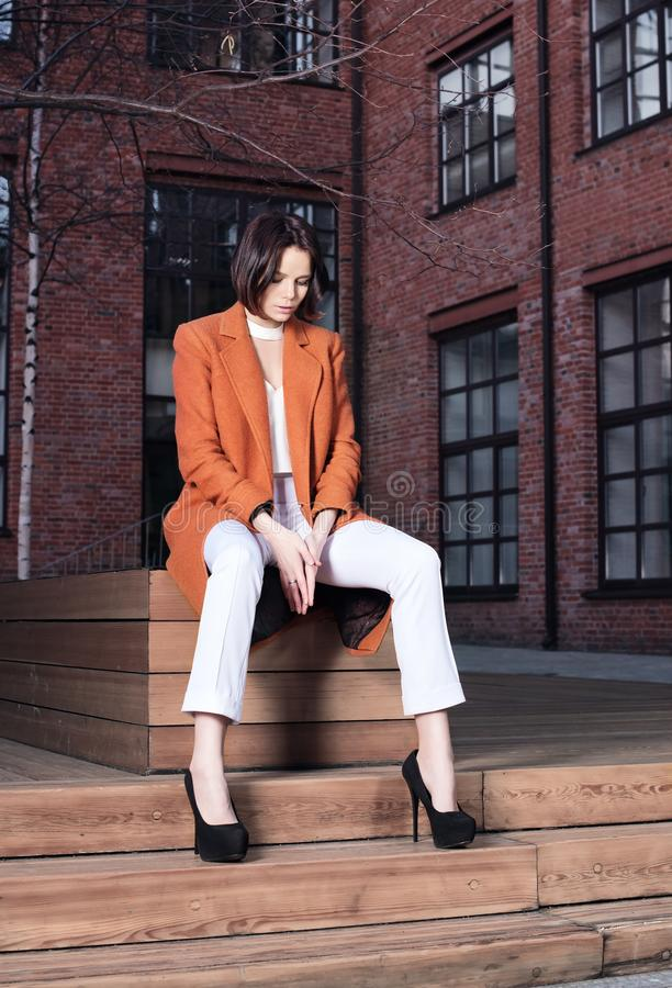 Young woman in red coat and white pants sitting on a wooden bench royalty free stock photos