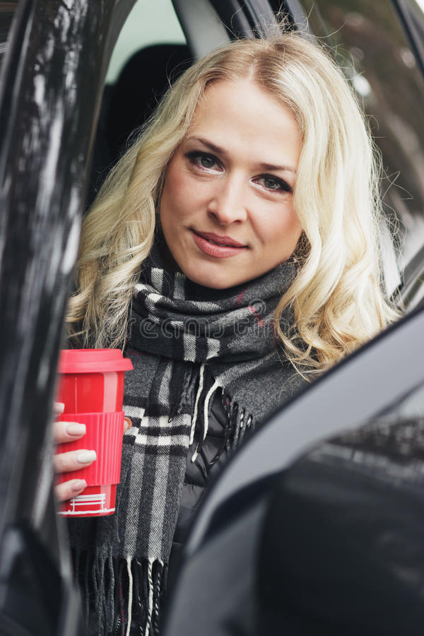 Young woman with a red cup sitting in the car. Young woman with a red cup of hot drink sitting in the black car, soft focus background royalty free stock photo