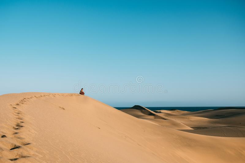 Young woman with red dress sit alone in the desert thinking and reflecting  on top of dune as a metaphor of loneliness and royalty free stock photo