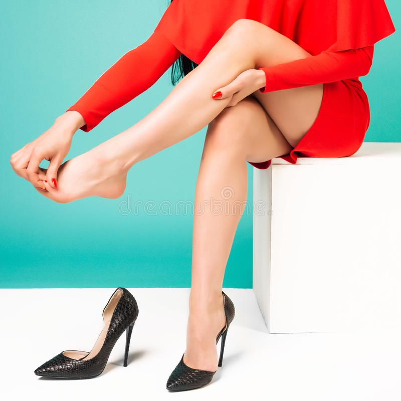 Young woman suffering from leg pain in office because of uncomfortable shoes stock image