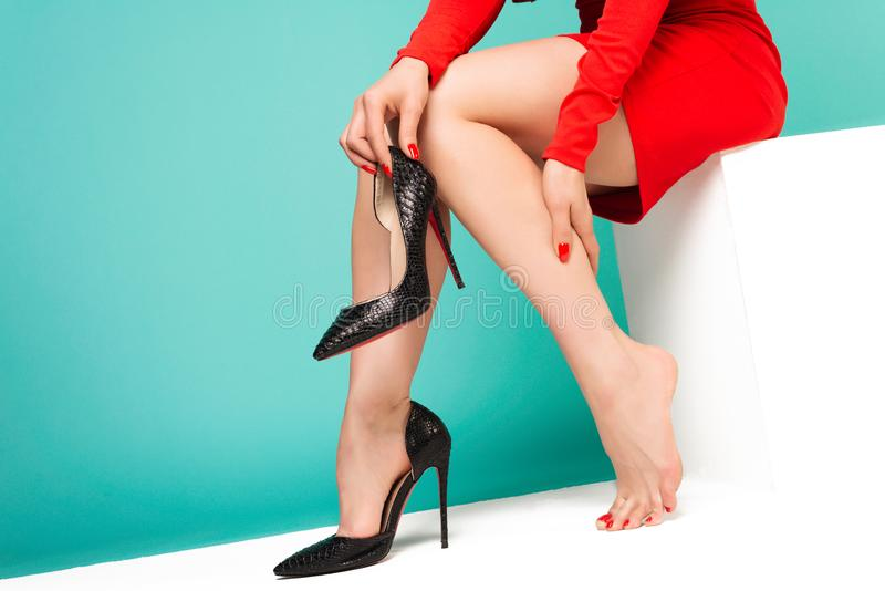 Young woman suffering from leg pain in office because of uncomfortable shoes royalty free stock photography
