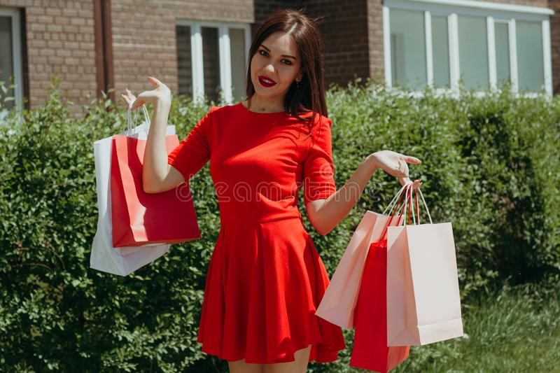 young woman in red dress walking down the street holding shopping bags royalty free stock photos
