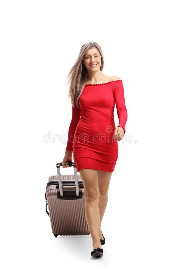 Young woman in a red dress walking towards camera and pulling a suitcase royalty free stock image