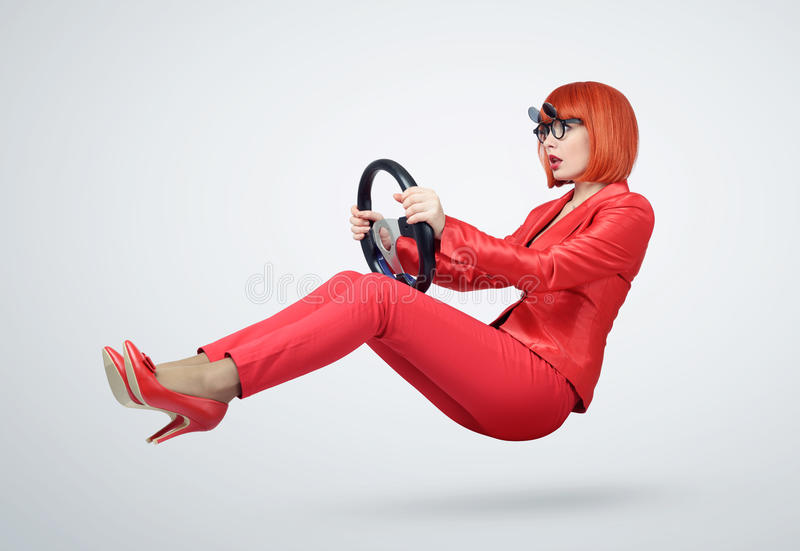 Young woman in red driver car with a steering wheel, auto concept royalty free stock image