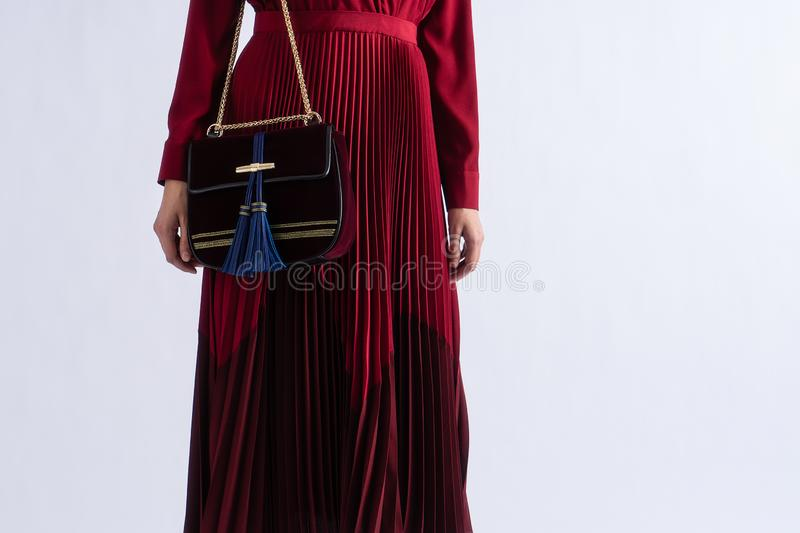 Young woman in red evening luxury pleated dress and luxury expensive bag. Posing on white background. Closeup with copy space royalty free stock images