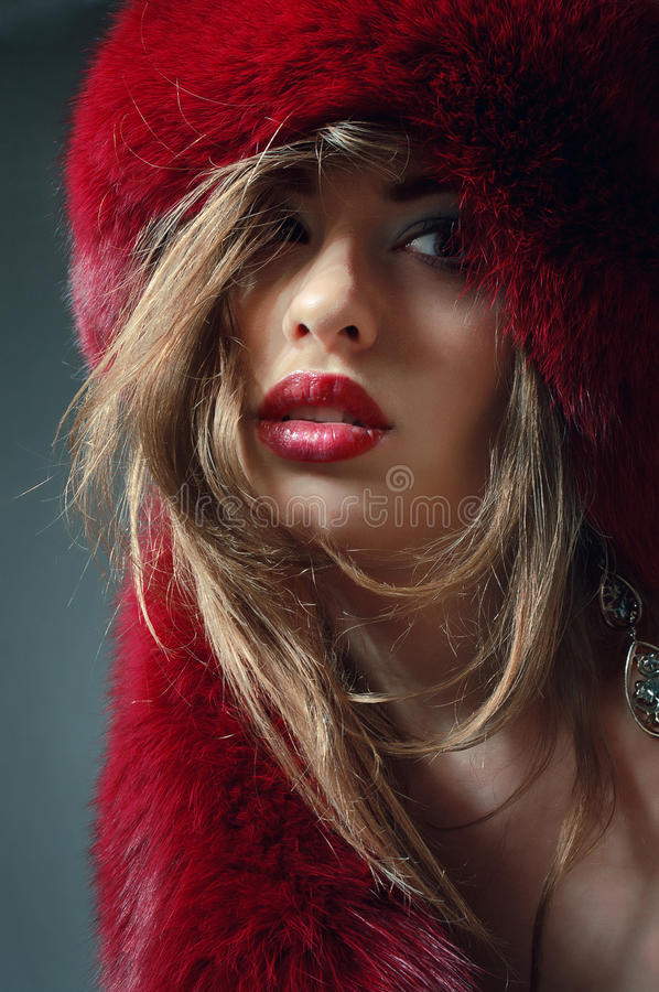 Young woman in red fur hat. Young blond woman in red fur hat royalty free stock images