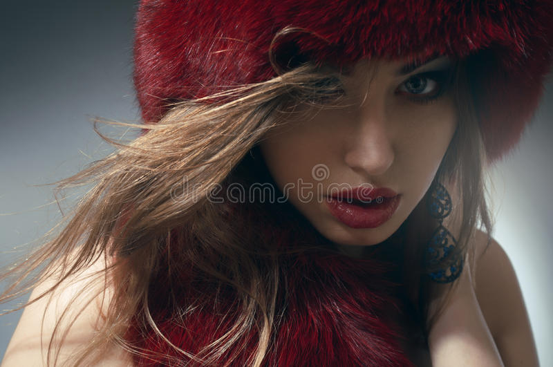 Download Young woman in red fur hat stock photo. Image of tanned - 20421762