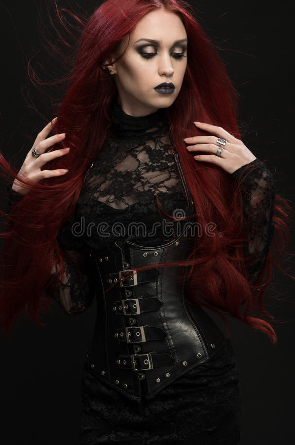 Young woman with red hair in black gothic costume. On dark background royalty free stock photo
