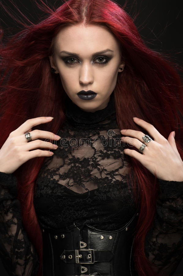 Young woman with red hair in black gothic costume. On dark background stock photo