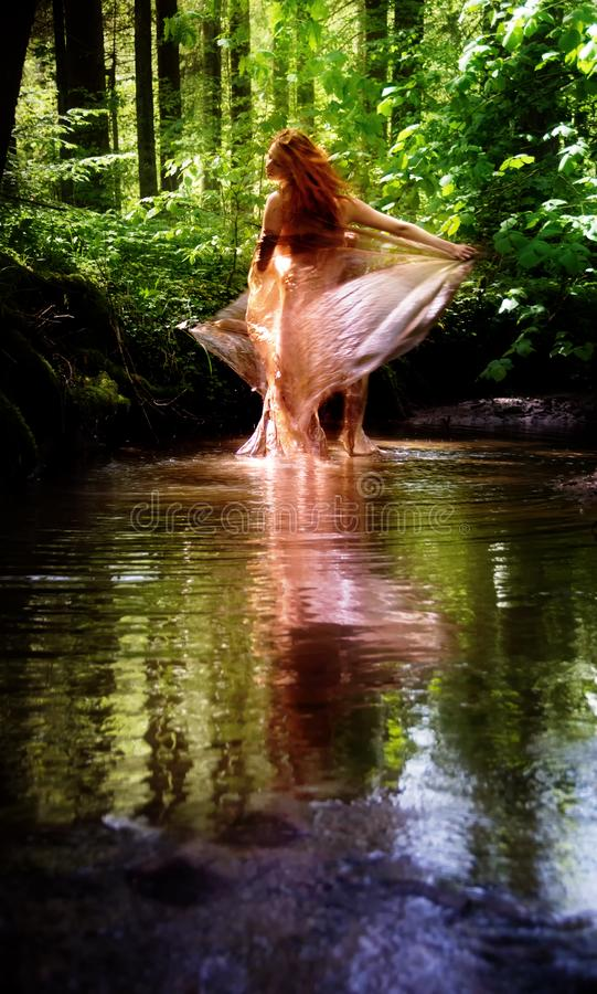 Young woman with red hair enjoying nature dancing in a river, copy space royalty free stock photos