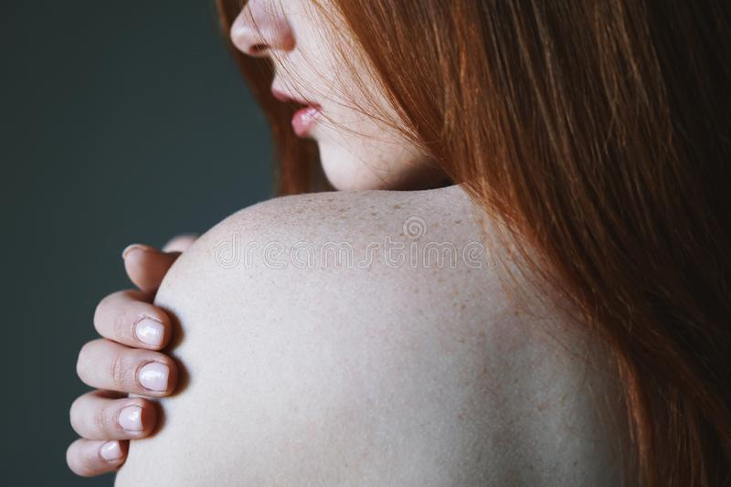 Young woman with red hair and freckles on bare shoulder. Skin or body care concept stock images