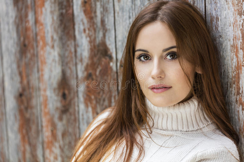 Young Woman With Red Hair Wearing Jumper. Outdoor portrait of beautiful girl or young woman with red hair wearing a white jumper royalty free stock photography