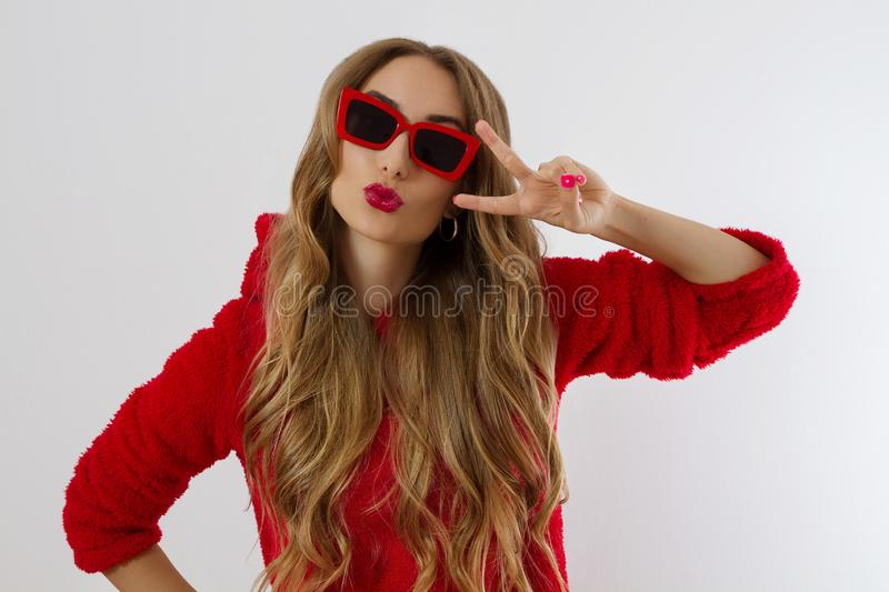 Young woman in red hoodie sweatshirt isolated on white background. Fashion and style concept. Peace sign gesture. Happy beautiful stock photo