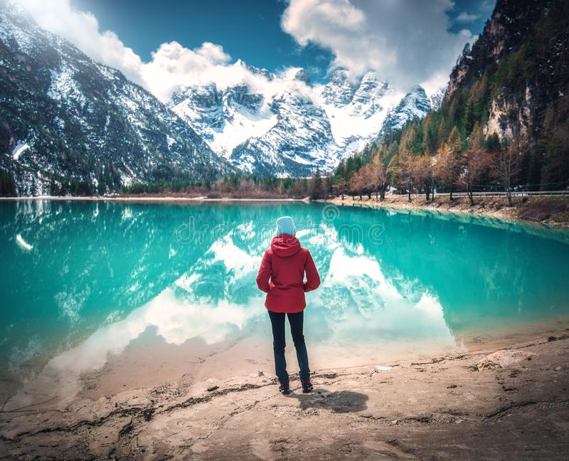 Young woman in red jacket is standing near lake with azure water. At sunny day in autumn. Travel. Landscape with slim girl, reflection in water, snowy mountains royalty free stock images