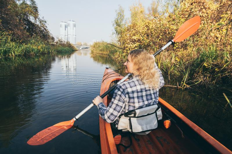 Young woman in red kayak rowing through the forest on the waters of Dnipro river in Kyiv, Ukraine. Young Caucasian woman in red kayak rowing through the forest royalty free stock photo