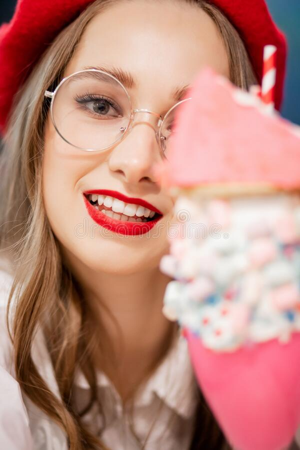 Young woman with red lips makeup, beret and glasses France eats sweet dessert in cafe stock images