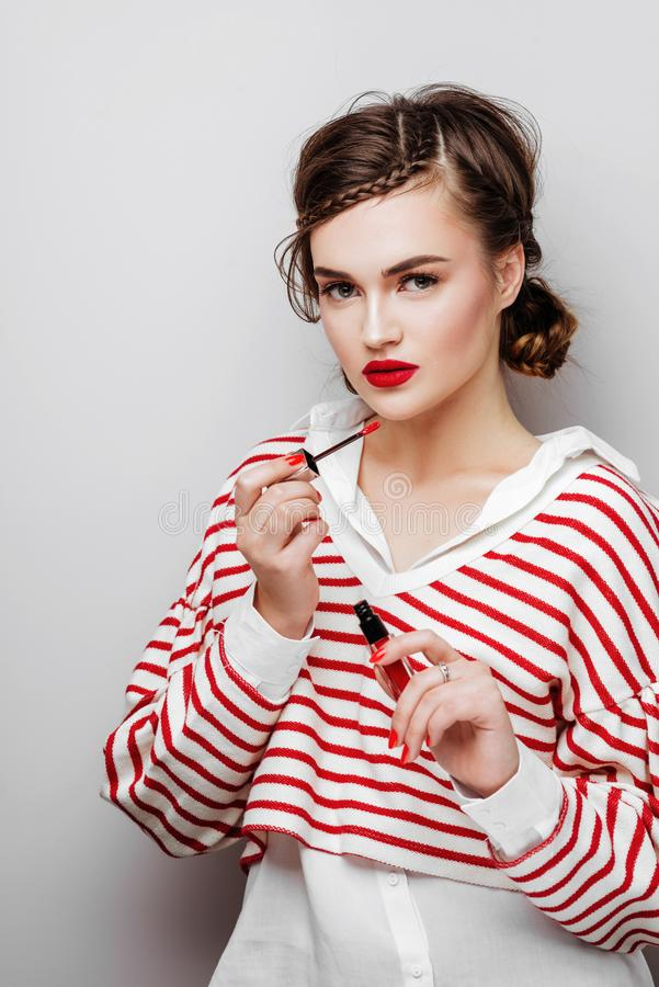 Young woman with red lips on pretty emotional face in elegant dress holding makeup lipstick in studio royalty free stock photography