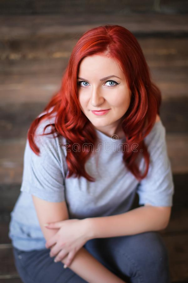 Young woman with red long hair indoor portrait on wooden background stock images