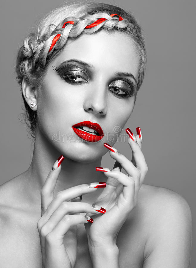 Young woman with red nails. Young blonde woman with braid hairdo and red nails on gray background stock photography