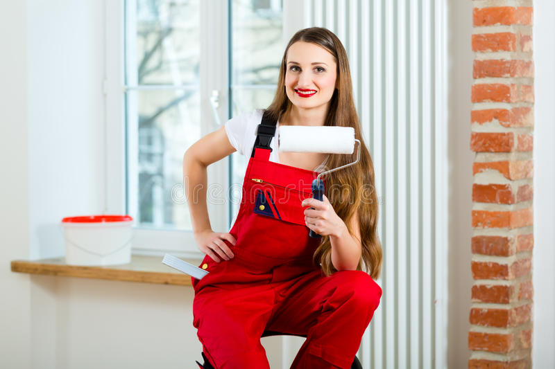 Woman renovating her apartment. Young woman in red overall renovating her apartment after she relocated to her new home royalty free stock photo