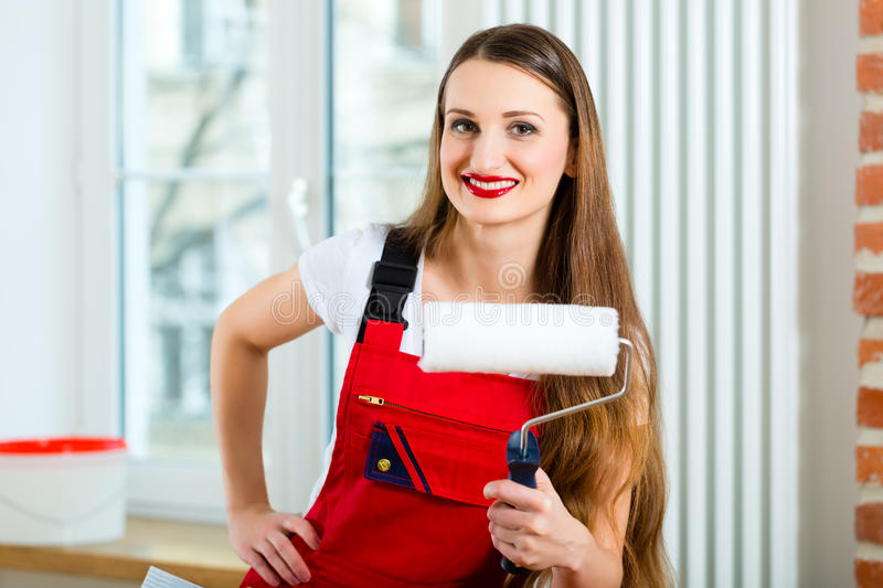 Woman renovating her apartment. Young woman in red overall renovating her apartment after she relocated to her new home stock photo